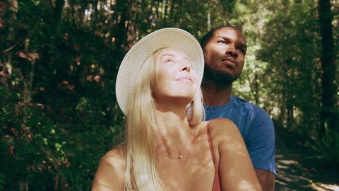 Young relaxed couple happily looking up and pointing in Australian rain forest through shaded green lush trees during daytime. Close up shot on 4k RED camera.