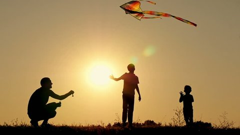 Happy father runs the snake into the air. Two children are playing, frolicking and jumping over a kite. Family unity, outdoor recreation. Slow motion