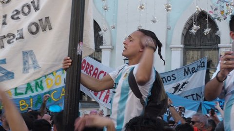 MOSCOW, RUSSIA, JUNE 20, 2018: Soccer World Cup Argentine football fans with flags at the on Nikolskaya Street, One of the fans climbed the pole and chanted the slogan. Crowd with mobile phones and