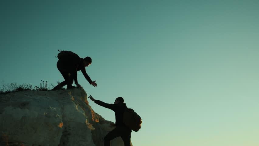 Silhouette hiker man tourists hands help climber climbs a mountain. walking tourist hiking adventure climbers sunset climb the mountain . slow motion video. hiker sunlight on top win victory the hill | Shutterstock HD Video #1018815049