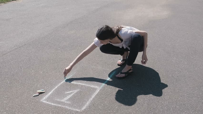Woman draws a hopscotch on the asphalt with colorful chalks.