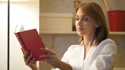Woman reads book at home, classical literature concept