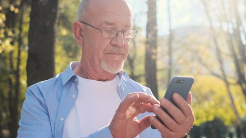 Portrait of senior man using mobile phone, holding device, texting, surfing internet, and using app. Senior man with a beard and wearing glasses looking at camera, smiling while rest in the park