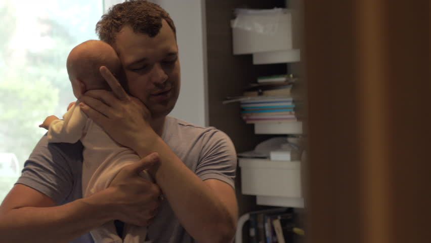 Young father holding gently two months baby daughter and lulling her to sleep, but child is awake and looking around. Dad enjoying moments | Shutterstock HD Video #1018920499
