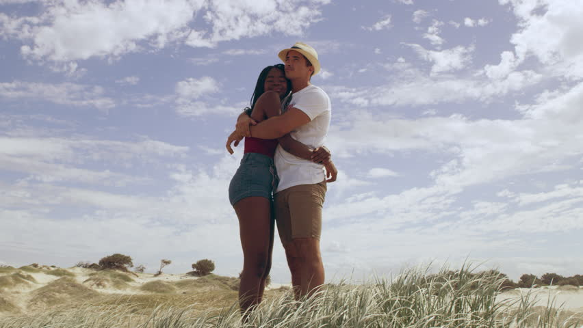 Young couple walking up to the top of a sand dune embracing each other in love, sand dunes and wide open sky in the background in Australia. Medium close up on 4k RED camera.