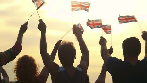 Patriotic UK crowd waving with flags outdoors. Group of cheerful people waving Union Jack flags. Fans at concert.