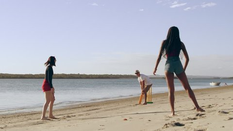 Friends casually playing cricket on the beach with sea and sun in the background in Australia. Wide shot on 4k RED camera.