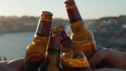 Celebration beer cheers concept - close up hands holding up glasses of beer of people group in outdoor party during their victory competition or successful task meeting vacation