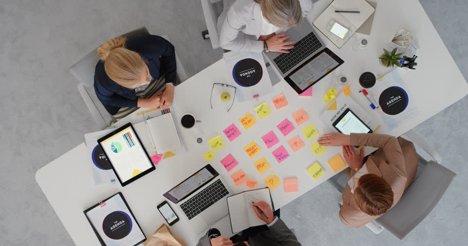 Group of diverse business people working together brainstorming strategy for innovative company making notes using colorful paper in boardroom meeting top view | Shutterstock HD Video #1019015359