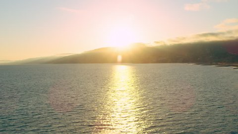 Aerial view of ocean shoreline during beautiful sunset in Los Angeles, California. Wide long shot on 4K RED camera.