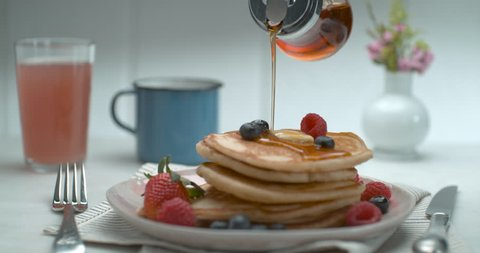 Maple syrup is poured over a stack of pancakes with fruit and butter on a table with a background in soft focus, in slow motion, in soft light. Closeup shot in 4K on a Phantom Flex