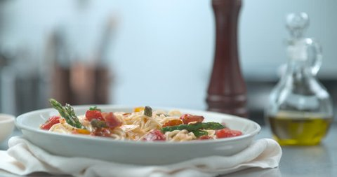 Italian Pancetta dropping onto spaghetti primavera dish in bowl in ultra slow motion with 4k Phantom Flex camera