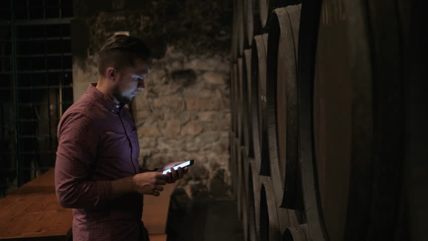 Old wine barrels in a wine cellar, sommelier man tourist dicover, porto, portugal, old factory stock phone tablet check quality port wine