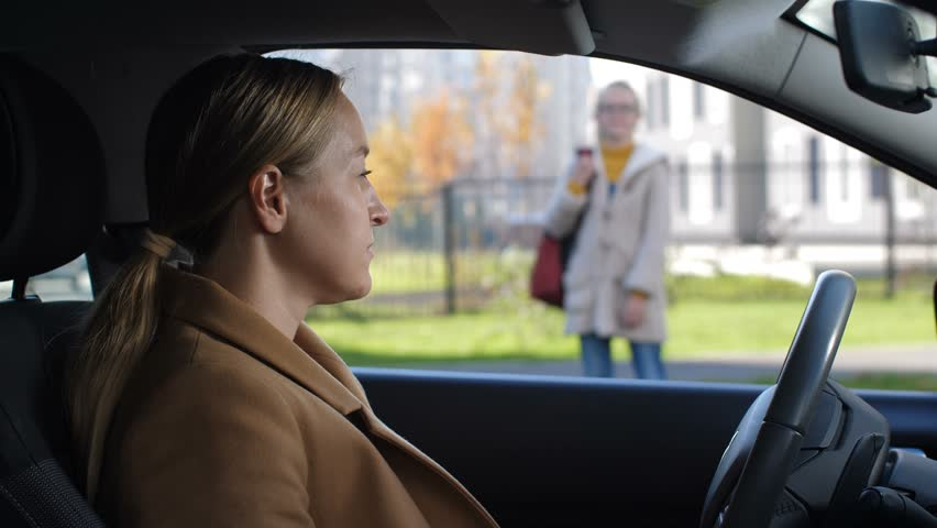Attractive adult mother greeting and kissing adorable schoolgirl after lessons outdoors while taking teenage daughter home from school by car. Loving mother driving her child home after school. | Shutterstock HD Video #1019044219