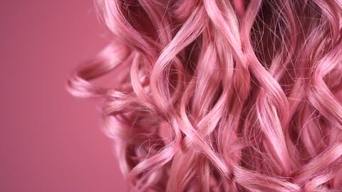 Hair. Beautiful healthy long curly dyed pink color hair close-up texture. Fashion trendy Dyed wavy hair background, coloring, extensions, cure, treatment concept. Haircare. Slow motion 4K UHD video