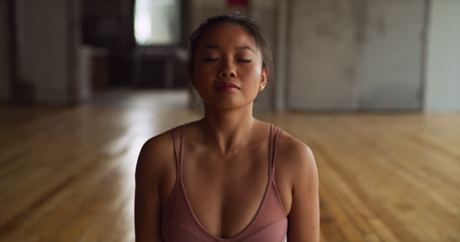 Yoga practitioner doing sun salutation in beautiful brick and beam industrial space during the day. Wide to medium shot on 4K RED camera.
