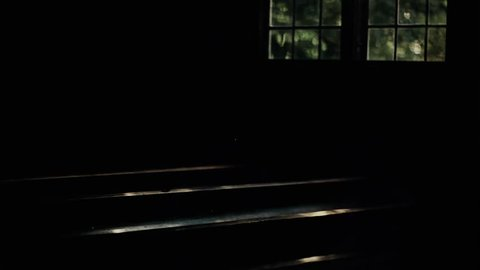 Pews and window in dark. Inside old, historic church; dark atmosphere and reflection of sun, sunlight from glass to pews.