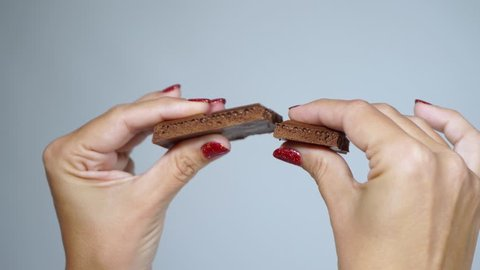 Closeup view on woman's hands breaking piece of chocolate isolated at light background. Fingernails manicured with beautiful red glossy gel polish. Real time full hd 4k video footage.