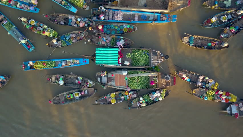 DRONE, TOP DOWN: Flying above local people doing business on the colorful floating market set on the calm murky river in the scenic Vietnamese countryside. People doing business on their wooden boats.