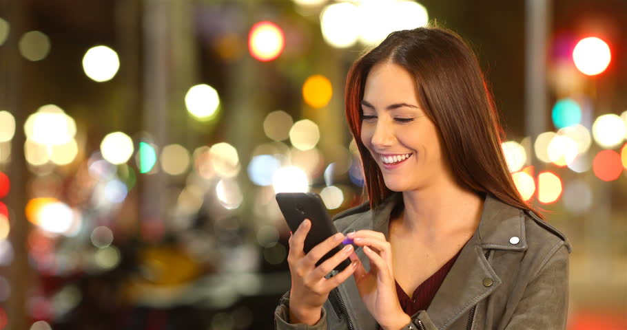 Fashion happy woman browsing smart phone content in the night in the street  | Shutterstock HD Video #1019123899