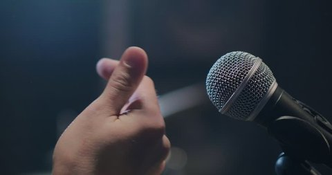 The musician setting the microphone and snapping rhythm with fingers