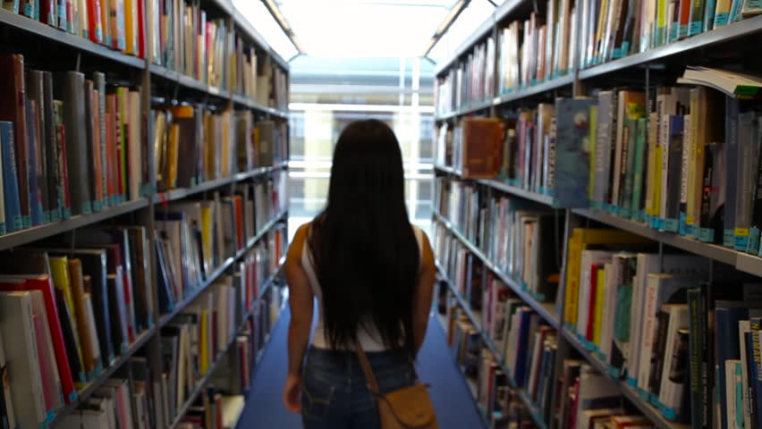 View of a Japanese girl from behind walking through bookshelves in a library | Shutterstock HD Video #1019172889