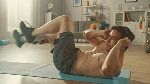 Strong Athletic Shirtless Fit Man in Grey Shorts is Doing Crisscross Crunch Exercises at Home in His Spacious and Sunny Living Room with Minimalistic Interior.