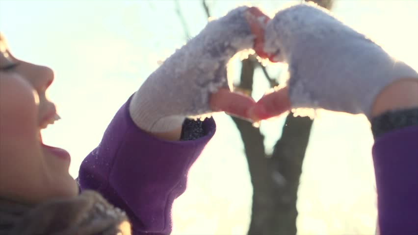Winter girl showing heart sign and smiling. Beauty Joyful Teenage Model Girl having fun in winter park. Beautiful young woman enjoying nature and laughing outdoors. Slow motion video footage 240 fps