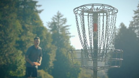Man Throwing Disc into Basket at Frisbee Golf Course