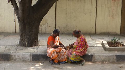HYDERABAD,INDIA-01 NOVEMBER,2018 Two Indian transgenders sitting on a sidewalk, counting money  in Hyderabad,India