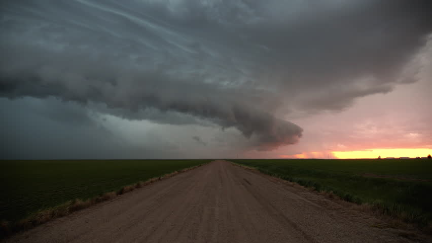 Dramatic storm clouds roll across the land over country road during colorful sunset in the grassy plains.