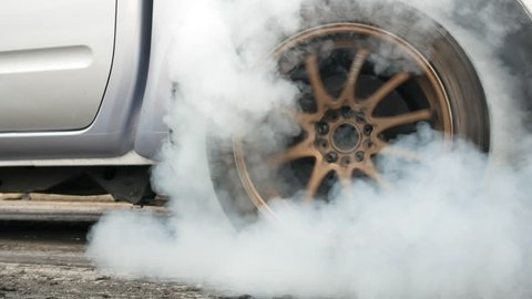 Drag car make tires warm up with smoke, Car racing burnout rubber off its tires in preparation for the race.