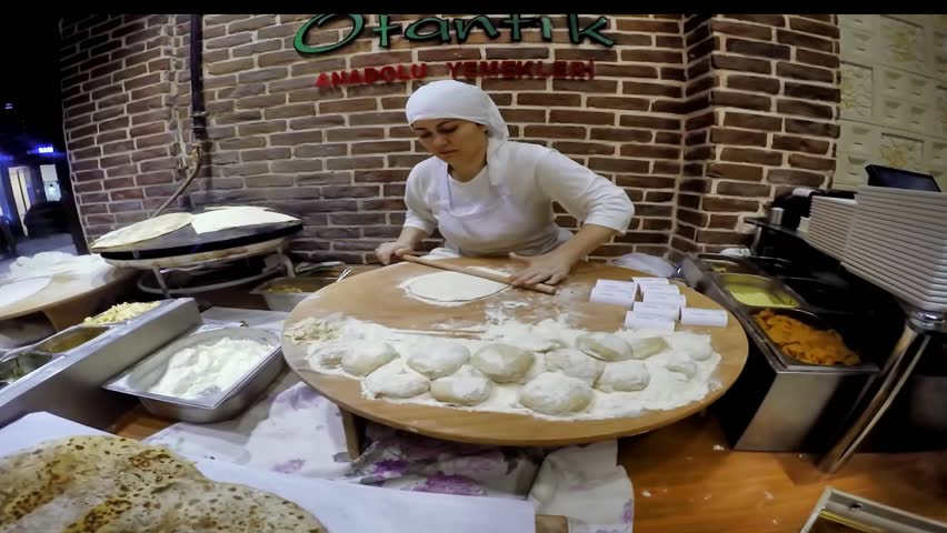 ISTANBUL, TURKEY - MAY 29, 2015: Ladies cooking gozleme in taksim Beyoglu. Gozleme is a savoury traditional Turkish dish made of hand-rolled dough that is lightly brushed with butter and eggs.