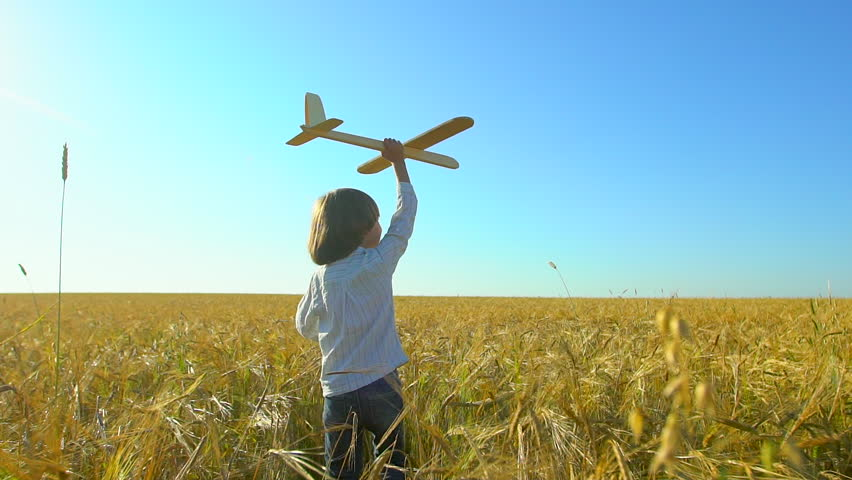 Happy little boy child running with toy airplane in wheat field at sunset. Kid playing with airplane in summer nature outdoors. Little pilot dreaming of flight, vacation with happy family, big dream. | Shutterstock HD Video #1019304469