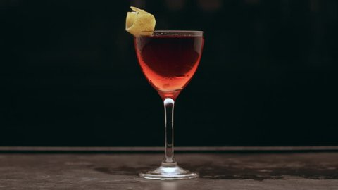 Negroni cocktail with garnish on a bar counter against a stark black background. Close up shot on 4k RED camera.