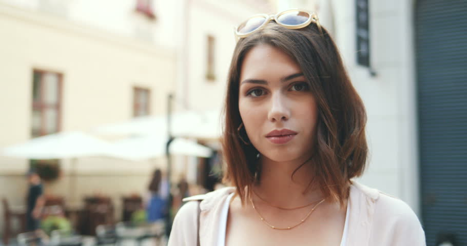 Portrait of the young beautiful woman with short hair smiling to the camera while standing at the street. Close up. Outdoor. #1019349109