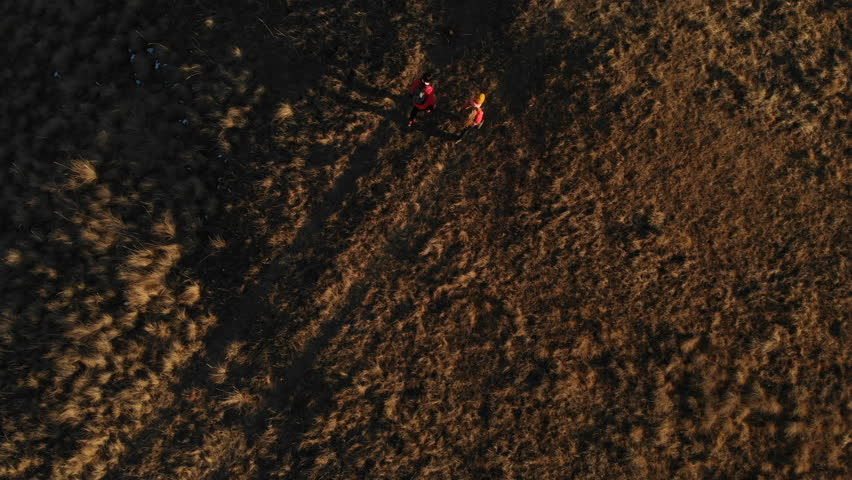 Aerial view of a two girls traveler with backpacks and cameras stroll through the hills between the epic rocks in the mountains. Girls photographers with their cameras at sunset   Shutterstock HD Video #1019366569