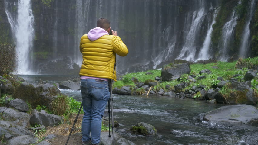 A Man Shooting Landscape photograph with his Mirrorless DSLR at Shiraito Falls in Fujinomiya City, Shizuoka Pref., Japan | Shutterstock HD Video #1019369179