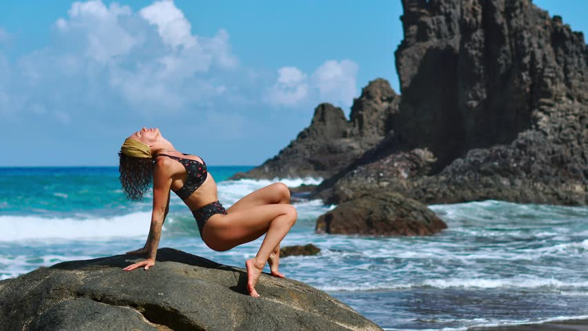 Young woman in bodysuit practicing yoga on the beach above sea at amazing sunrise. Fitness, sport, yoga and healthy lifestyle concept. Girl doing stand on head and twine. | Shutterstock HD Video #1019371129