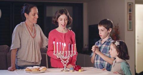 Kids and their mother lighting Hanukka candles