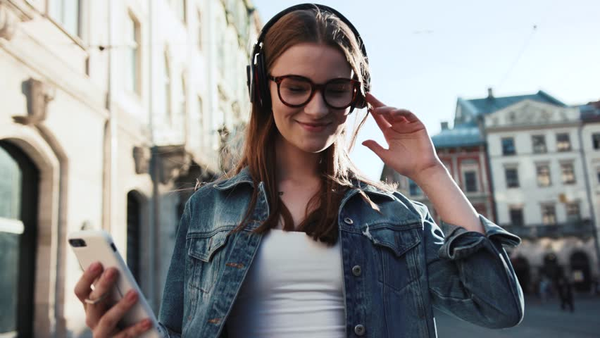 Smiling young woman with glasses listening to music in headphone use smartphone at city walk sunset look around close up portrait slow motion | Shutterstock HD Video #1019386009
