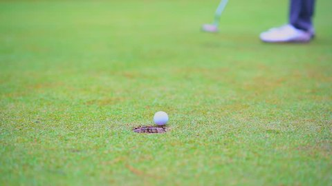 Golf sport concept, Slow motion golfer putting golf ball to hole in open tournament on beautiful golf course on hills