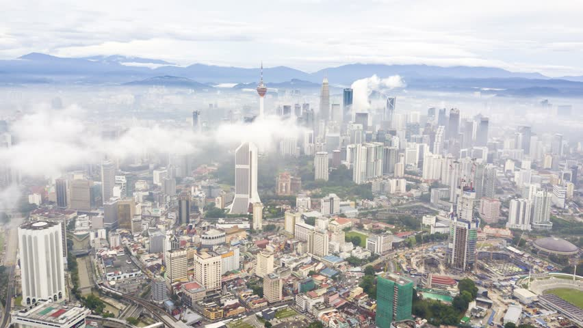 Cinematic aerial time lapse of rolling low clouds over Kuala Lumpur tall buildings and landmark during sunrise. Zoom out | Shutterstock HD Video #1019427649