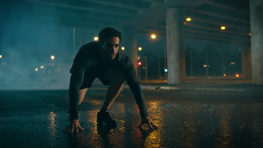 Strong Muscular Fit Young Man Starts Sprinting on a Rainy Evening. He is Running in an Urban Environment Under a Bridge with Cars in the Background.