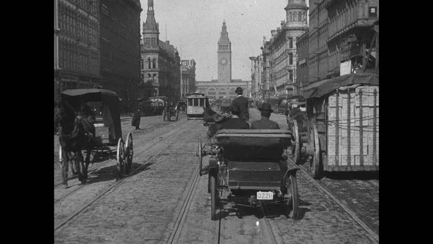 1900s: Cars and horse drawn carriages travel down city street. Cable car travels along tracks down street. People walk around city.