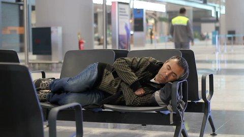Young man sleeping while waiting the plane at airport passenger terminal