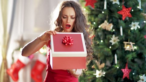 young woman in red dress near Christmas tree getting shocked after opening Christmas present box. Bad xmas gifts concept. Unhappy xmas.