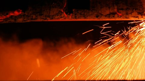 Gas cutting of steel pipes metal factory interior. Sparks flying steel pipes production. Gas cutting metal sheet with bright sparkle in factory.
