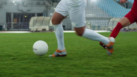 Focus on Legs of a Professional Soccer Player Leading with a Ball, Masterfully Dribbling Around His Opponents. Two Professional Football Teams Playing on Stadium. Low Angle Ground Shot.
