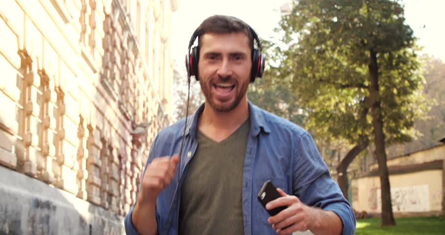 Smiling and Laughing Man listeting Music from Smartphone and Dancing on Street. Happy Man looking to the Camera,walking on street of old Town City Center in Europe. Sunny Day. Attractive People. #1019549659